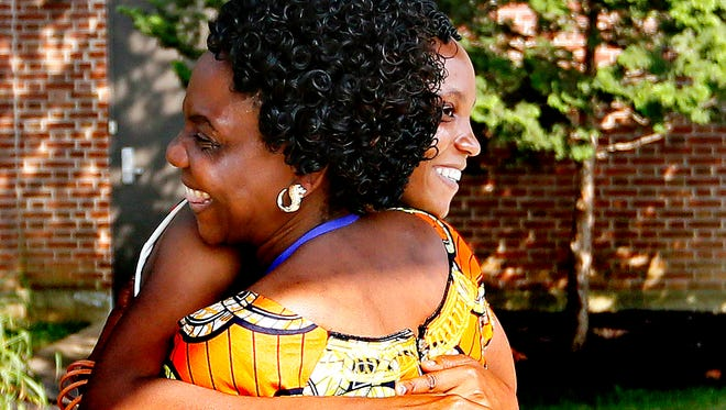 Congolese refugee Elizabeth Abeca, back, hugs her mother, Anyesi Chala, upon her arrival at the Lancaster Airport in Lititz, Monday, July 25, 2016. Abeca, 24, arrived on June 29 with her 2-year-old daughter, Mlasi Tipa, and has been waiting for her parents and siblings to arrive from the refugee camp in Tanzania where they have lived for nearly 20 years. Stony Brook Mennonite Church has gathered resources for the family and will help ease their integration process. Dawn J. Sagert photo
