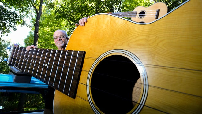 Larry Stump stands in the back of his  1959 Chevy Apache truck with is his giant ukulele - the world's largest - Wednesday, Sept. 15, 2016 at his house in Dimondale. At 13 feet, one inch long, the ukulele  is in the Guinness Book of World Records as the largest in world.  Stump said it took him about two months to make the uke from birch plywood, for the body, and select wood for the neck. The instrument is exactly 7.5 times bigger than a normal ukulele, which is resting on the body of giant uke.
