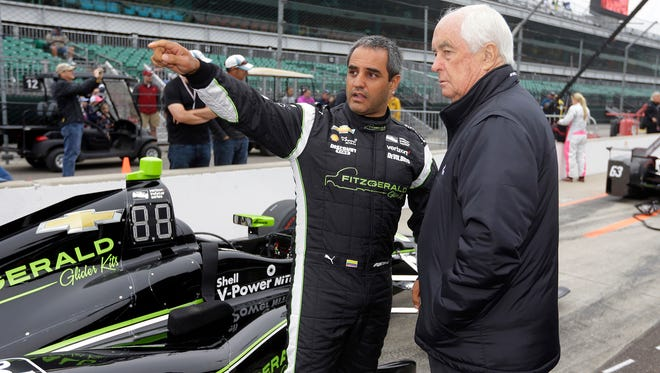 Juan Pablo Montoya talks with car owner Roger Penske before the start of qualifications for the Indianapolis 500.