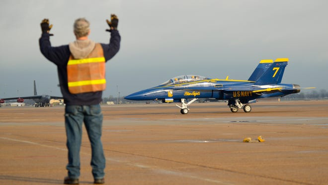 A ground crew member at Barksdale Air Force Base directs a Navy Blue Angel jet on the ramp Monday.