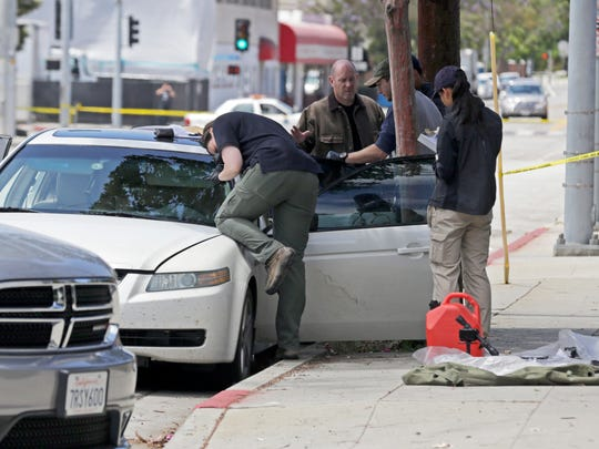Investigators record the scene from a car belonging to a heavily armed man after he was arrested in Santa Monica, Calif., early Sunday, June 12, 2016.