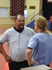 Marianas Sports Officials Association's referees Frank Cruz, left, and John Halloran, right, speak with each other during a basketball game at St. John's School in Tumon on Jan. 10.