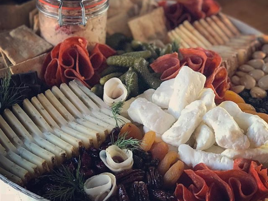 A cheese tray featuring artisan meats, fruits and spreads