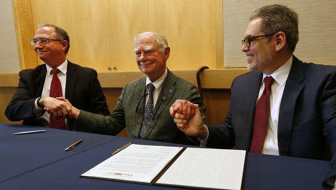 "From left, Terry Egger, publisher and CEO of Philadelphia Media Network, H.F. ""Gerry""  Lenfest, chairman of PMN, and Pedro A. Ramos, president and CEO of The Philadelphia Foundation, hold hands after signing an agreement at the National Constitution Center in Philadelphia on Jan. 12, 2016. Lenfest announced that he will be donating PMN, the holding company for The Philadelphia Inquirer, Daily News and philly.com, to the Philadelphia Foundation, a newly created non-profit media institute."