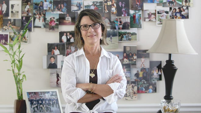 Fort Myers resident Melissa Crouse, pictured by a wall of family photos Monday, October 26, has been battling lung cancer for 10 years. Crouse deals with the stigma of lung cancer even though she has never smoked.