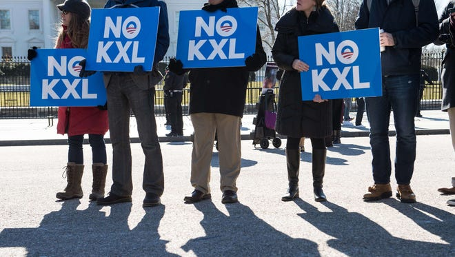 In this Jan. 28, 2015, file photo, demonstrators hold signs against the proposed Keystone XL pipeline from Canada to the Gulf of Mexico in front of the White House.