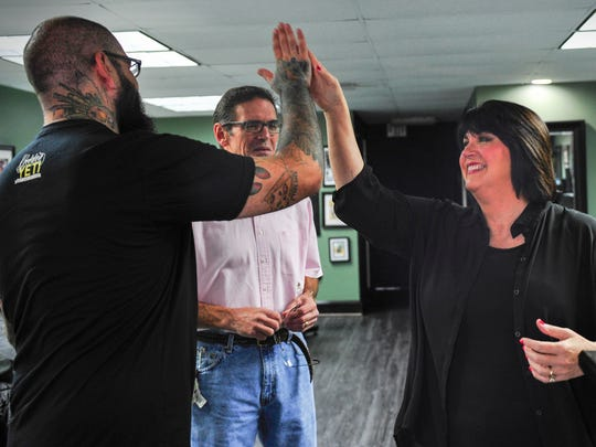Tattoo artist Jeff Barnard gets a high five from breast