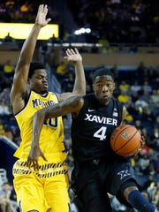Edmond Sumner of the Xavier Musketeers drives to the basket against Derrick Walton of the Michigan Wolverines during the second half at Crisler Arena on Nov. 20, 2015 in Ann Arbor.