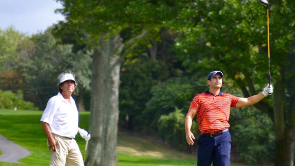 Michael Karger (right) watches his drive fade into