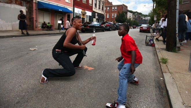 Jennifer Dukes dances with her son, Fray Chaney, 8, both of East Price Hill, dance during the CIRV open house block party on an afternoon in Over-the-Rhine in 2011. CIRV is refocusing its aim after top officials left the group to aid in the reform at the University of Cincinnati's police force.