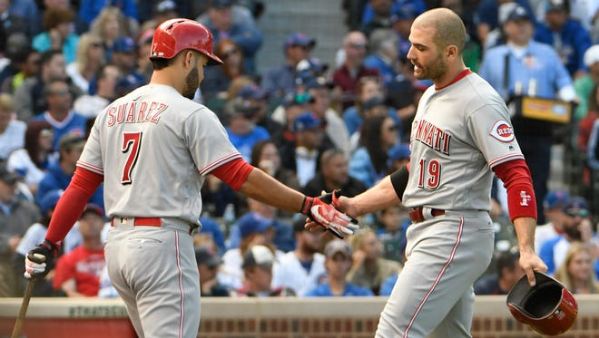 The Cincinnati Reds' Joey Votto (19) is greeted by Eugenio Suarez (7) after scoring against the Chicago Cubs during the fourth inning of the game Sunday, Oct. 1, 2017, in Chicago.