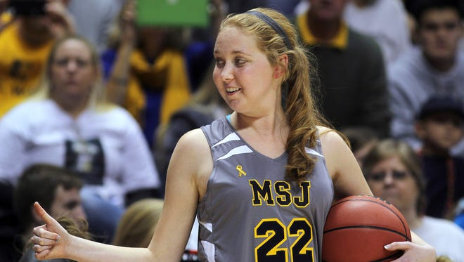 FILE - In this Nov. 2, 2014, file photo, Mount St. Joseph's Lauren Hill gives a thumbs-up as she holds the game ball during her first NCAA college basketball game, against Hiram University, at Xavier University in Cincinnati. The 19-year-old freshman basketball player died at a hospital in Cincinnati Friday, April 10, 2015, the co-founder of her foundation The Cure Starts Now said. (AP Photo/Tom Uhlman, File)