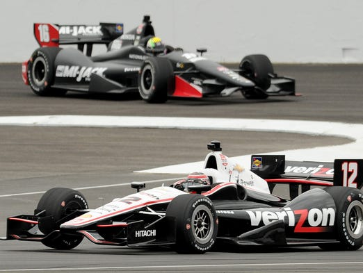 Will Power (12) and Oriol Servia (16) in the first turn during the IndyCar road course test at the Indianapolis Motor Speedway, Wednesday, April 30, 2014, in Indianapolis.