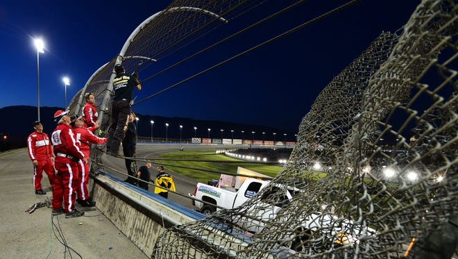 Track crews work on repairing the fence between turns 3 and 4 after a crash during final practice for the Verizon IndyCar Series MAVTV 500 IndyCar World Championship Race at the Auto Club Speedway on August 29, 2014 in Fontana, California.