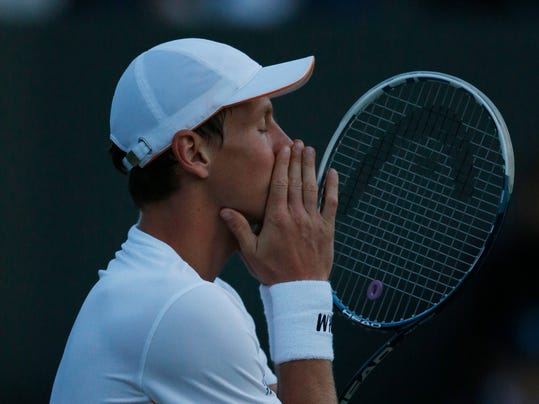 Tomas Berdych of Czech Republic complains to the umpire about the fading light conditions during the men's singles match against Marin Cilic of Croatia at the All England Lawn Tennis Championships in Wimbledon, London, Friday June 27, 2014. (AP Photo/Ben Curtis)