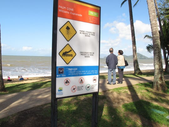 A sign warns of the dangers of crocodiles and marine stingers in the Pacific Ocean beach community of Palm Cove, Australia. Northeastern Australia has miles of nearly empty beaches, but many warn of crocodiles and marine stingers. The threat is different in different times of the year. In response, many beaches have designated swimming areas that are protected by nets.