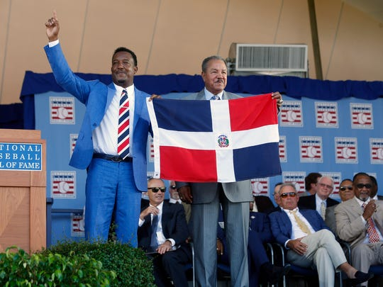 National Baseball Hall of Fame inductee Pedro Martinez, left, holds the flag of the Dominican Republic with countryman and fellow Hall of Famer Juan Marichal during an induction ceremony at the Clark Sports Center on Sunday, July 26, 2015, in Cooperstown, N.Y. (AP Photo/Mike Groll)