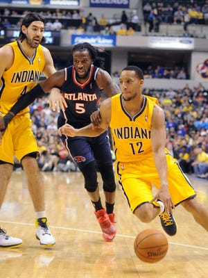 Evan Turner uses a screen by Luis Scola to get around Hawk defender DeMarre Carroll. The Indiana Pacers hosted the Atlanta Hawks in NBA action Sunday April 6, 2014 at Bankers Life Fieldhouse.