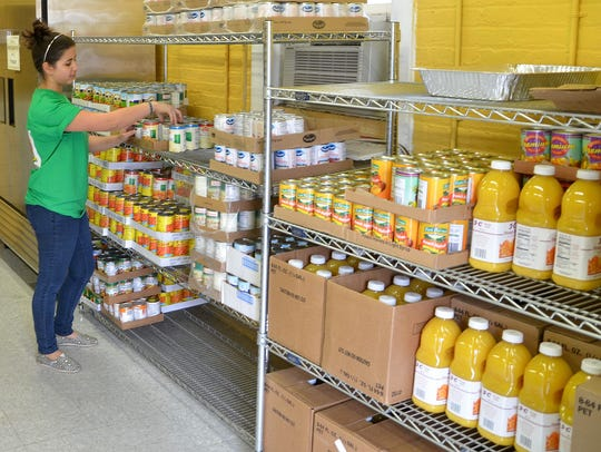 A volunteer stocks a shelf at a food pantry run by
