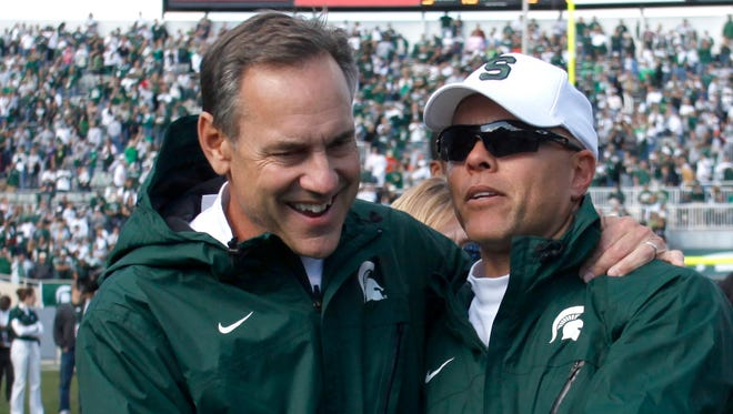 Mark Dantonio, left, and Don Treadwell celebrate Michigan State's win over Illinois on Oct. 16, 2010. Treadwell returns to MSU this fall as an assistant coach.