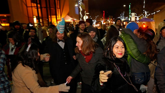 From right, Lisa Pena, Carli Romero, Buddy Trujillo and Mary Nunez dance while celebrating the new year during the  New Year's Eve Street Party and Chile Drop Event in Las Cruces, N.M., Thursday, Jan 1, 2015.