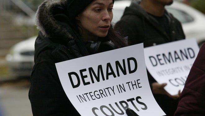 Leah Schommer of Green Bay holds a placard during a protest outside the Sheboygan County Courthouse Thursday, Nov. 2, 2017. An estimated more than 70 demonstrators backing an investigator's efforts to launch a John Doe investigation in Sheboygan County took part in the roughly hour-long demonstration.