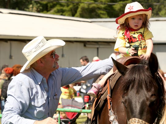 Volunteer Raymond Grahn helps steady Karlee Murphy, 2, atop a horse as she takes a ride during Corey's Day on The Farm at the Kitsap County Fairgrounds on Monday, May 14, 2018.
