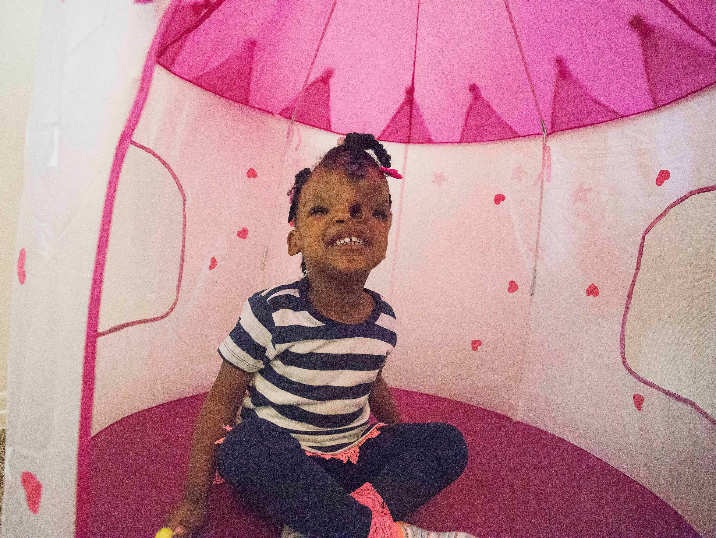 Zoey Grace Alford gives a big smile while playing in her pink castle.