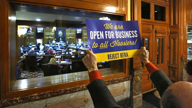 A protestor holds up a sign opposing the Religious Freedom Restoration Act outside the House chamber on March 23, 2015.