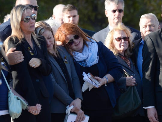 Sonja Overall, far left, is consoled by family members at the end of the memorial service for her husband, Oakland County sheriff's deputy Eric Overall, on Nov. 28, 2017 in Independence Township.
