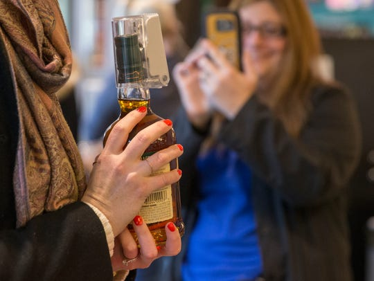 Customers take photos on the first day of legal universal Sunday carry-out alcohol sales in Indianapolis on March 4, 2018.