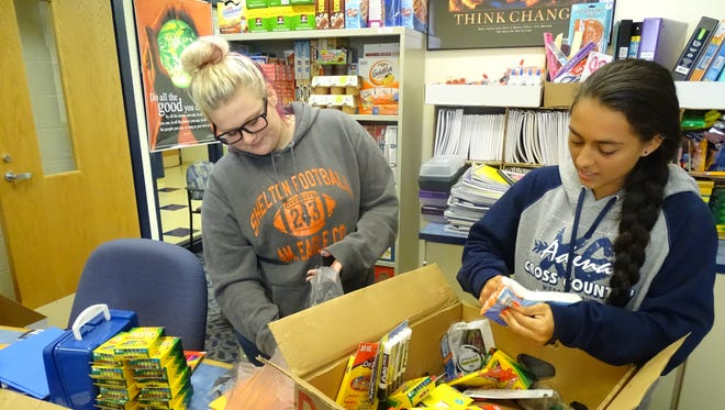 Jasilyn Conley, left, and Angel Merk, right, are Adena High School seniors who volunteer part of their school day to organize and stock donations to the school store.