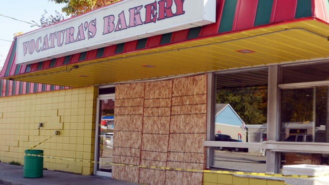 Plywood covers the  area where a jeep crashed through the front of Vocatura's Bakery in Norwich Sunday.