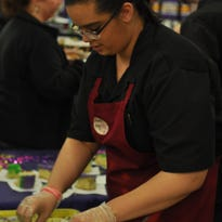 Alex Rashall serves king cake from Atwood's Bakery Friday evening at Taste of Mardi Gras