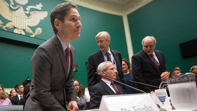 Centers for Disease Control and Prevention director Dr. Tom Frieden, left, takes his seat on Capitol Hill in Washington before testifying Thursday before the House Energy and Commerce Committee's subcommittee on Oversight and Investigations, which was seeking answers about the Ebola outbreak from top U.S. health officials.