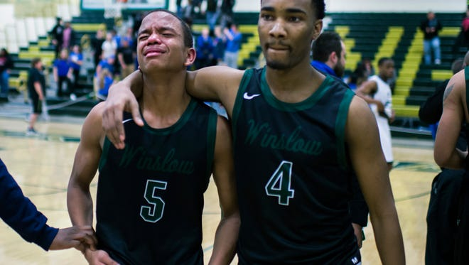 Winslow's Ronnell Garrett (4) consoles teammate Sidney Brown (5) after a 58-49 loss against Ewing in a state Group 3 semifinal Wednesday, March 8 in Brick.
