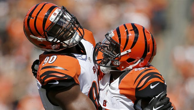 Bengals defensive ends Michael Johnson (left) and Wallace Gilberry celebrated Gilberry's sack and fumble of San Diego Chargers quarterback Philip Rivers.