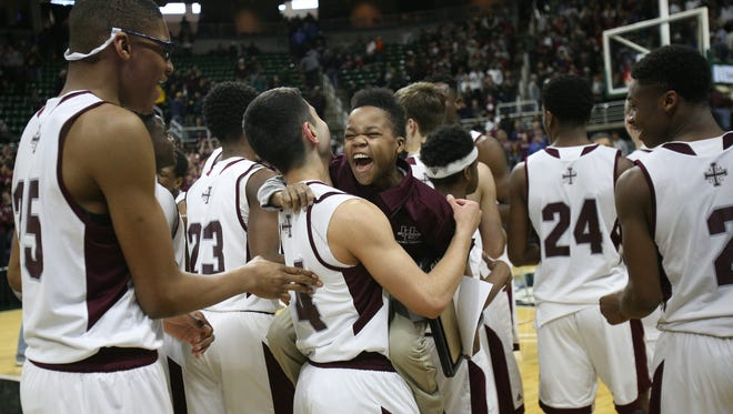 Detroit U-D Jesuit manager Alford Harris is embraced by Matt Schearer after defeating North Farmington 69-49, during the MHSAA boys basketball Class A finals at the Breslin Center in East Lansing on Saturday, March 26, 2016.