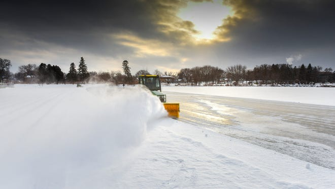 A crew from the St. Cloud Parks and Recreation Department starts clearing the fresh snow Thursday, Dec. 28, off Lake George, which officially opens for skating at 4 p.m. Friday.