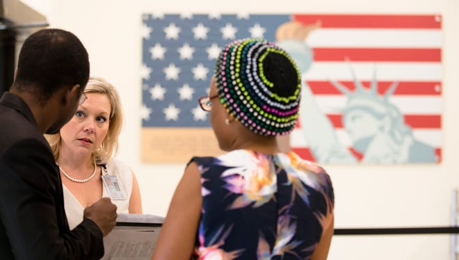 Stephanie Greene speaks to two clients at the U.S. Citizenship and Immigration Services field office in Montgomery, Ala., on Tuesday, June 13, 2017.