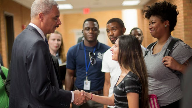 Attorney General Eric Holder shakes hands with Bri Ehsan, 25, right, following his meeting Wednesday with students at St. Louis Community College-Florissant Valley in Ferguson, Mo.