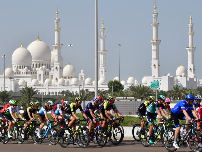 The peloton rides past Sheikh Zayed Grand Mosque during