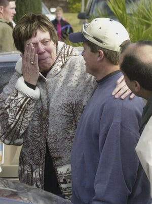 Jule Cook wipes away a tear as she's consoled by family friend Jason Fox Jan. 11, 2005 in St. George. Cook's home was one of several claimed by flood waters from the Santa Clara River.