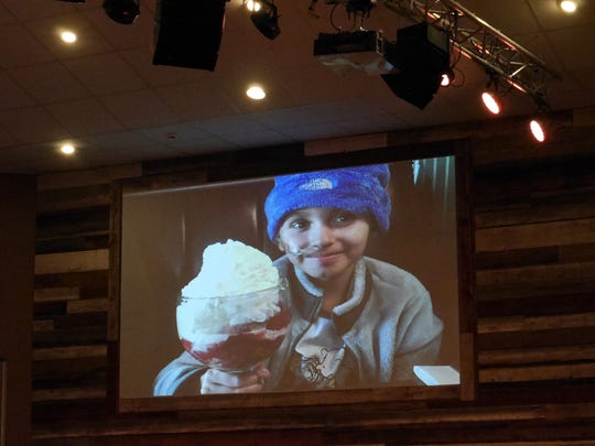 A photo on a large screen of Meredith Furr enjoying an ice cream sundae welcomes her friends and familyto a candlelight vigil celebrating her life at the Destiny Family Center, Stuarts Draft Sunday March, 13, 2016. Furr died after a difficult fight with cancer.