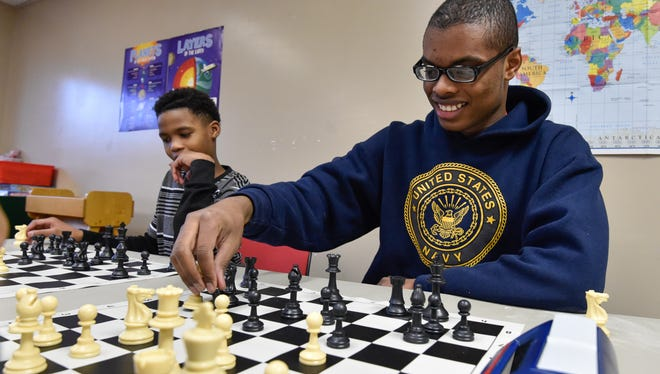 Johnny Means, right, 16 a junior at Delaware Military Academy is changing the way kids are thinking, one chess game at a time. This 16-year-old Delaware Military Academy student shares his knowledge and love of the game after school at the Neighborhood House.