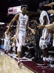 The FSU Men's basketball team stands and congradulates Ike Obiagu (12) and M.J. Walker (23) on good shifts against Georgia Tech on Wed., Jan 24th at the Donald L. Tucker Center.