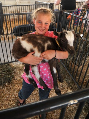 Avery Lassa of Merrill holds up her goat at the 2015 Lincoln County Fair in Merrill.