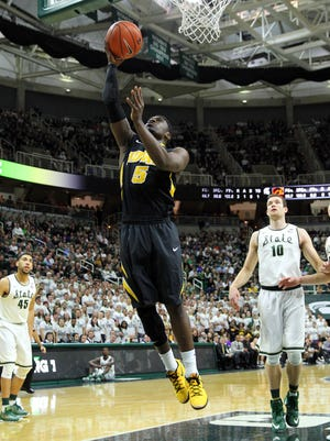 Iowa senior guard Anthony Clemmons (5) gets a layup as MSU's Matt Costello (10) and Denzel Valentine watch Thursday at Breslin Center. Clemmons scored 13 points to help the Hawkeyes beat the Spartans and his former Sexton High teammates Valentine and Bryn Forbes for the second time this season.