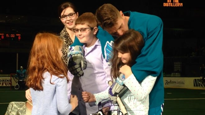 Sgt. Jesse Fuller, second from right, hugs his children after surprising them at a Knighthawks game on Dec. 12, 2015.
