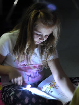 Riley Schmidt, a second grader at Fowler Elementary, uses a flashlight to help her read a book in a darkened classroom set up to simulate camping out during the school's Read 2 Learn rally.